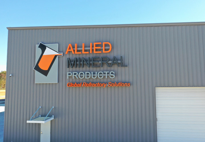 Exterior detail of Allied Mineral Product's industrial facility, closeup on logo
